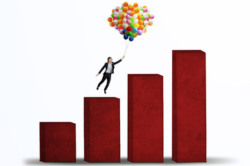 Businesswoman flying with balloons over graph isolated