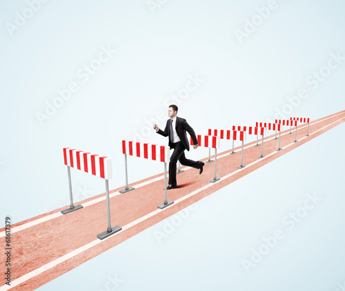 businessman jumping over barrier