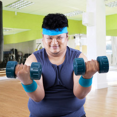 Fat man exercise in fitness center 3
