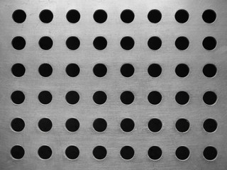 Metal plate with many circular holes background.