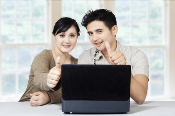 Happy couple and laptop showing thumbs up