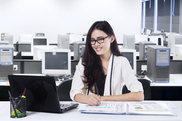 Pretty woman smiling at camera in office