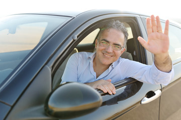 smiling man sitting in his new car