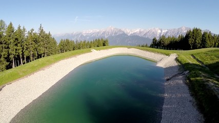 Flying over a small mountain lake - Aerial Flight