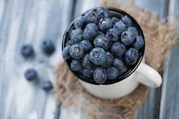 Ripe blueberries in a cup, wooden background, high angle view