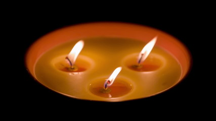 Three Candles in the dark  with flare flame