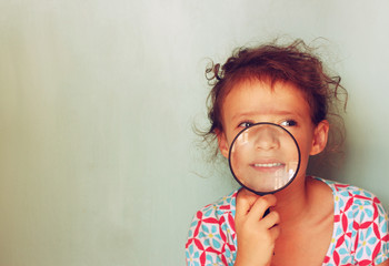 cute kid looking through magnifying glass