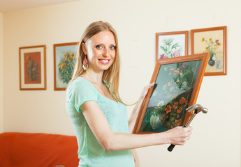 Happy girl hanging art pictures