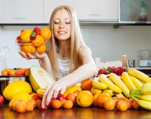blonde long-haired woman choosing  fruits