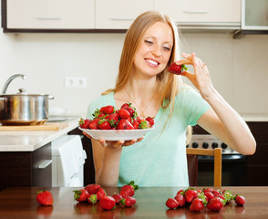 Happy  woman eating strawberry