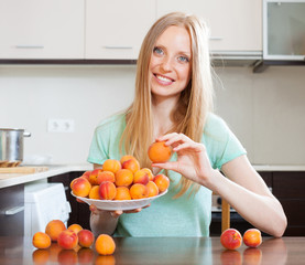blonde long-haired girl holding apricots in home kitchen