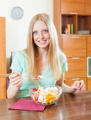 long-haired woman eating  fruit salad with yoghurt