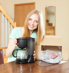 Happy young woman with new  coffee maker in home interior