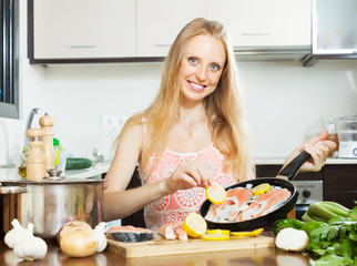Smiling girl cooking salmon fish with lemon