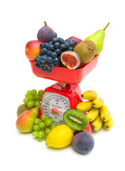 Fresh fruit and kitchen scale on white background.