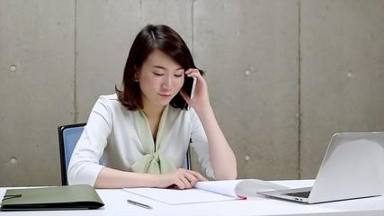書類を見ながら電話するビジネスウーマン