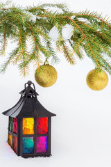Decorative lantern in the snow and fur-tree branch with Christma