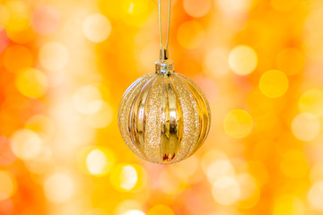 Christmas ball on a background of yellow and orange bokeh