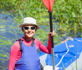 Happy cute girl holding paddle near a kayak