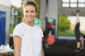 Smiling young woman rests at the fitness gym