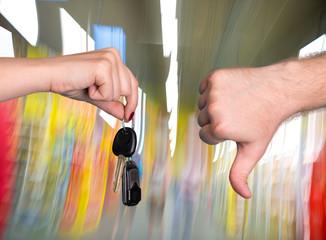 Woman holding car key, man showing thumb down