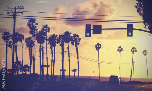 Retro Vintage sunset picture of palms and poles on street against sun.