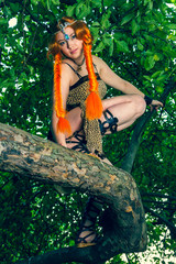 Beautiful red head woman sitting on a tree