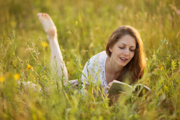 Happy woman lying on the grass and reading a book