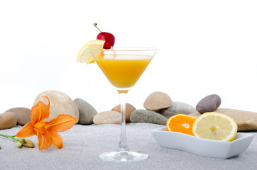 Composition with a orange cocktail, sand and pebble stones