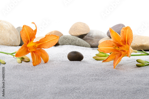 Pebble stones and orange lily flowers on gray sand