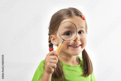 canvas print picture Little Girl Looks Through Magnification Glas