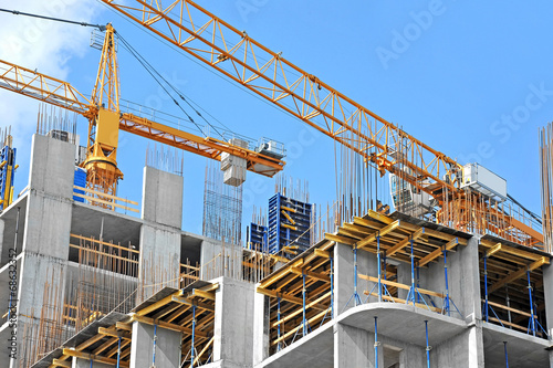 Poster Stad gebouw Crane and building construction site against blue sky
