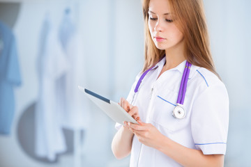 beautiful young female medical intern with tablet computer