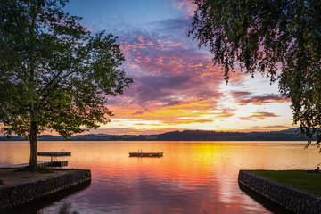 moody sunset at lake wallersee in austria with trees