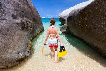 Woman with snorkeling equipment at tropical beach