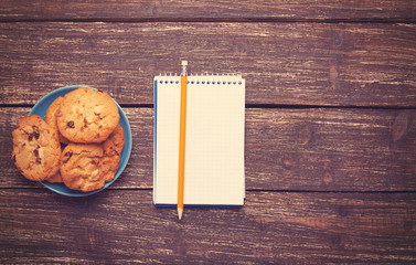 Cookie and pencil and notebook.