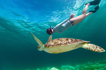 Young woman snorkeling with sea turtle