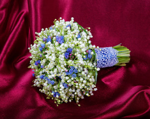 Wedding bouquet from lilies of the valley on a red fabric