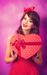 Beautiful brunette girl with heart shape gift on violet backgrou