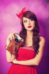 Beautiful brunette girl with retro camera on violet background.