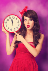 Beautiful brunette girl with big clock on violet background.