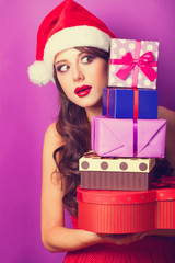 Beautiful brunette girl in christmas hat with gifts  on violet b