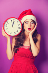 Beautiful brunette girl in christmas hat with huge clock on viol