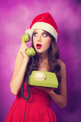 Beautiful brunette girl in christmas hat with green telephone on