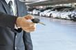 Businessman hand giving a car key - car sale & rental concept