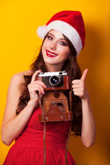 Beautiful brunette girl in christmas hat with camera on yellow b