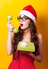 Beautiful brunette girl in christmas hat with telephone on yello