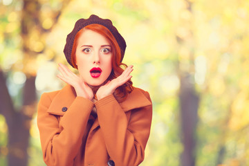 Redhead girl in autumn park