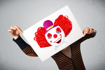 Woman holding a cardboard with a clown on it in front of her hea