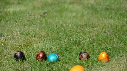 family Easter game with painted colorful eggs on grass.